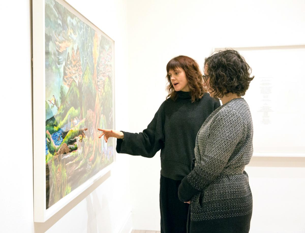 Artist Emily Vey Duke speaks with a Patron during the member's opening of The Illuminations Project.