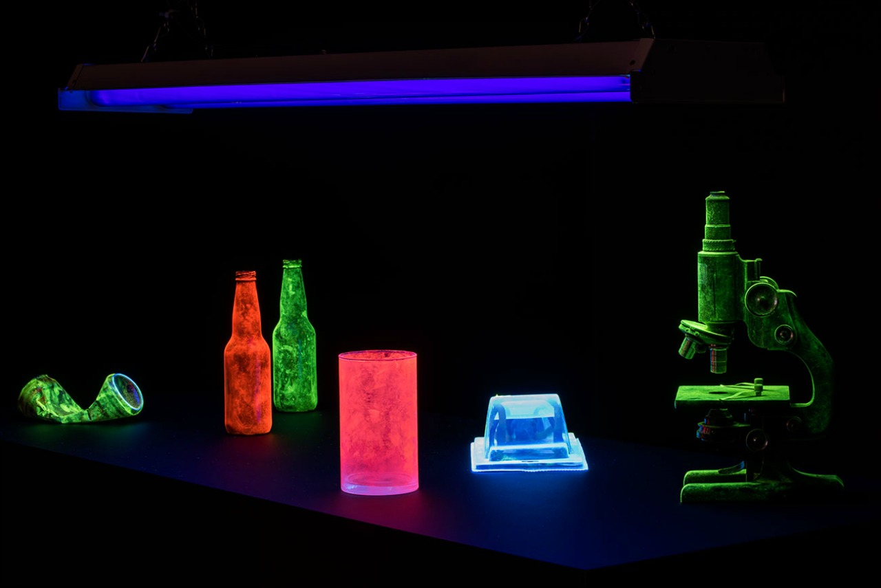 Installation view of: Angela Glanzmann, On the Matter, 2015, found objects, police grade fingerprinting powder, UV lights. Dimensions variable. Photo: Steve Farmer